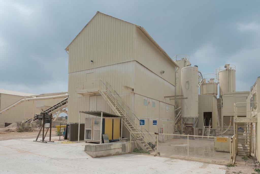 Bâtiment abritant l'usine de micronisation. Au centre de l'image, juste derrière le silo se cache le local où se concentre l'unité de production du ciment. [©ACPresse]