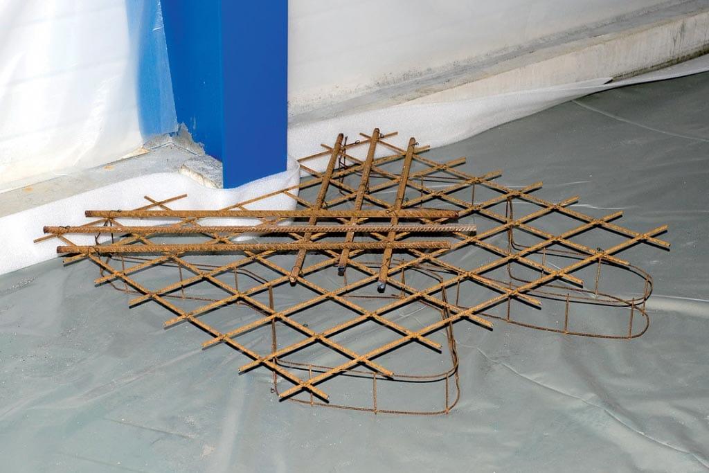 Renfort d'armature sur un dallage désolidarisé au droit d'un poteau. [©Lafarge]