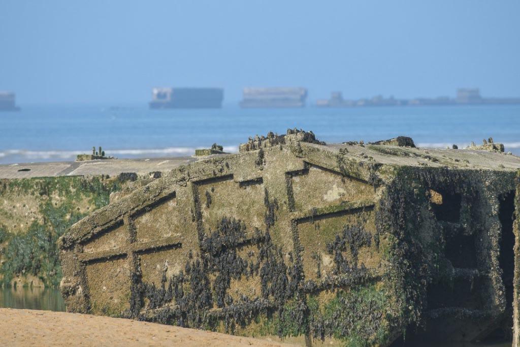 Sur la plage d'Arromanches gisent encore les carcasses des flotteurs en béton des routes flottantes. [©ACPresse]