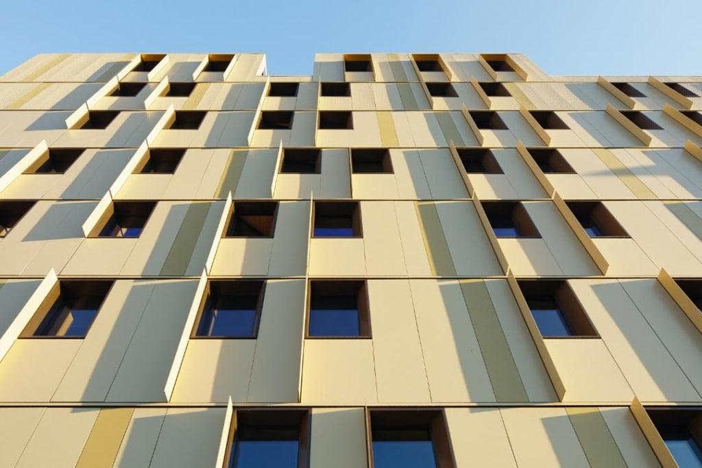 Les bardages en aluminium anodisé ne laissent pas imaginer la structure en bois. [©Takuji Shimmura]