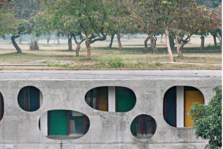 """Le Palais de l'Assemblée (38 m de haut à son point culminant) se trouve à l'extrémité Nord-Ouest de la cité de Chandigarh. Ce bâtiment est moderne par ses piliers, de forme rectangulaire, qui soutiennent un """"avant-toit"""" arrondi, creusé, comme une gouttière, et par son toit plat auquel on a accès, et qui comporte un cône en béton de 40 m, sous lequel se trouve la salle où les députés de l'Assemblée se réunissent. [©Manuel Bougot ©F.L.C._ADAGP, Paris, 2019, pour l'ensemble des œuvres de Le Corbusier ©ADAGP, Paris, 2019, pour l'ensemble des œuvres de Pierre Jeanneret]"""