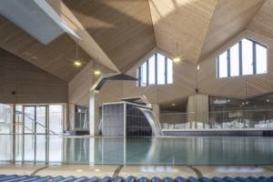 Ce n'est pas du Lignotrend : la piscine de Chambéry tout juste inaugurée (ALN architecture) magnifie le plafond acoustique en bois linéaire prolongé en bardage intérieur (Ecoteam, Lifteam), qui le rend plus actuel que jamais. [©Tommaso Morello/Grand Chambéry]