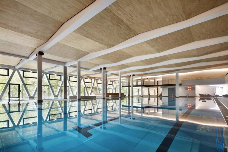 Le plafond qui ne fait pas de vagues et qui fait des vagues : pour cette piscine, le plafond Lignoakustik est posé en dent de scie grâce à la disposition des lisses en bois fixées sur les poutres en béton. [©Lignotrend]