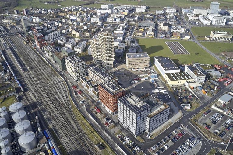Bilan carbone : Le quartier de Suurstoffi à Risch-Rotkreuz s'étend sur 10 ha sur une friche industrielle en bordure de la voie ferrée. Au premier plan, Suurstoffi 22, pionnier des tours à structure bois de moyenne hauteur en Suisse. Et au tout premier plan, en marge du quartier, les groupes de refroidissement du réseau de chaleur. [©Zug Estates]
