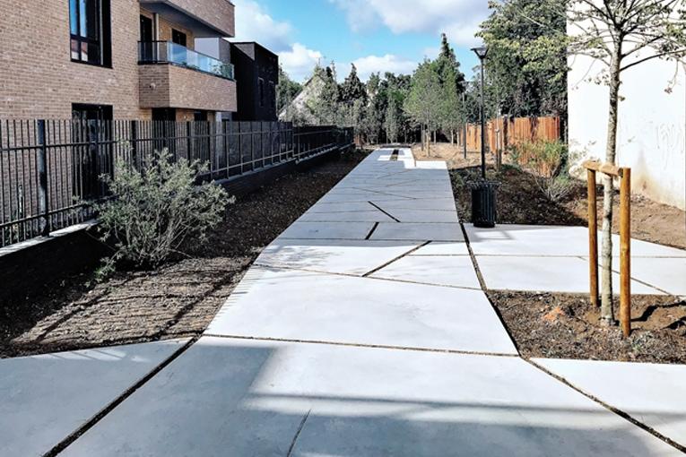Le long des logements tout juste sortis de terre prend place une rue-jardin, qui dégage une vaste perspective incitant à la flânerie.  [©Eurotech Floor]