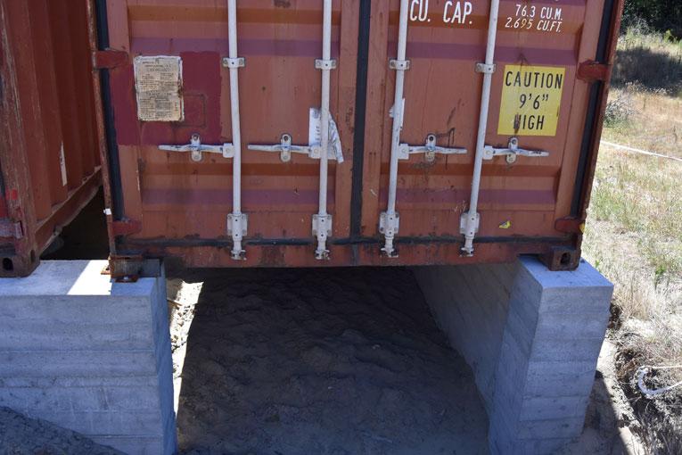 Les conteneurs reposent sur des fondations maçonnées, qui ménagent un important vide sanitaire. [©Gérard Guérit]