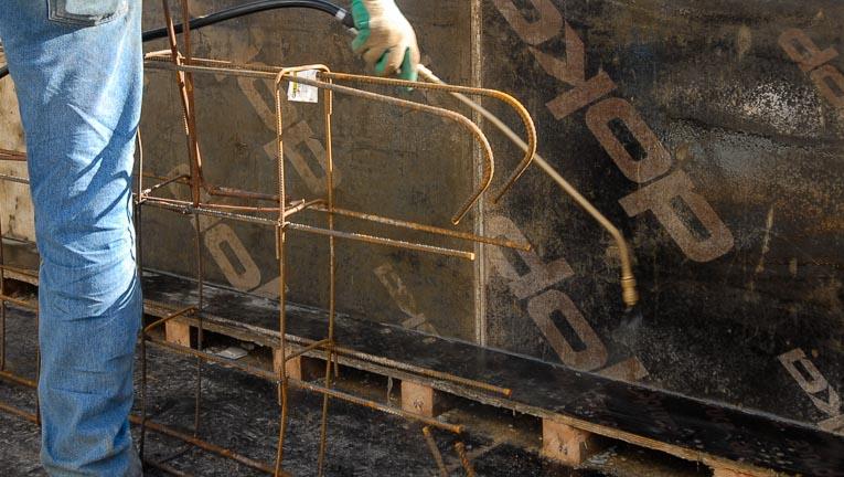 Application d'un agent de démoulage à l'aide d'un pulvérisateur. [©ACPresse]