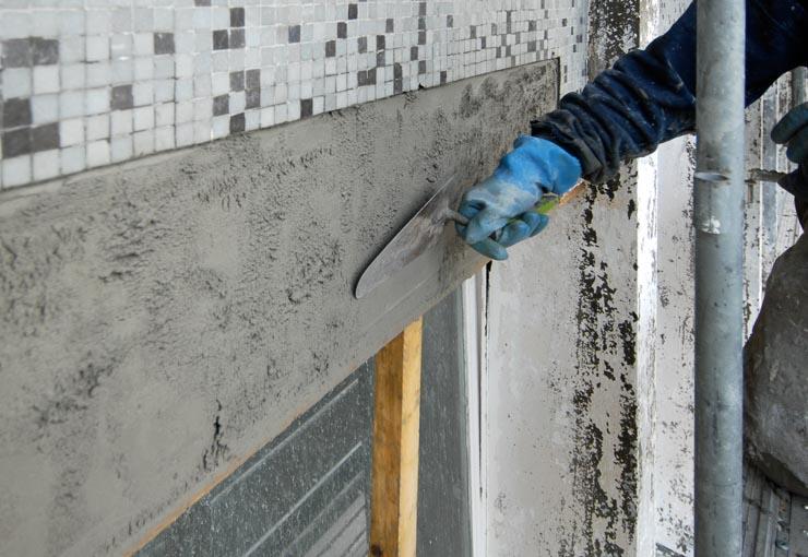 Mise en œuvre d'un mortier de réparation dans le cadre de la rénovation des façades d'un bâtiment. [©ACPresse]