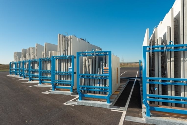 Murs à coffrage intégré positionnés dans des racks, prêts à être livrés sur chantier. [©ACPresse]