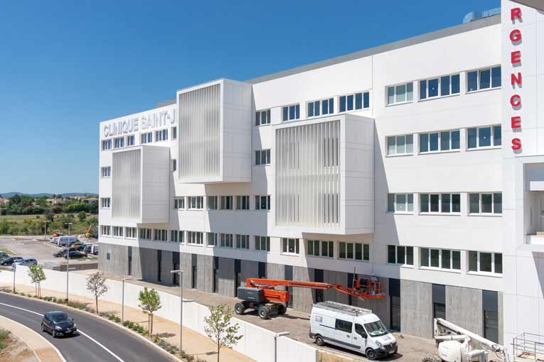 Les façades en béton blanc sont posées sur un socle en béton gris matricé. [©ACPresse]