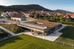 La Maison de la jeunesse et des sports est comme intégrée dans le terrain, qui l'enveloppe jusque sur la toiture-terrasse. [©RHB Architectes]