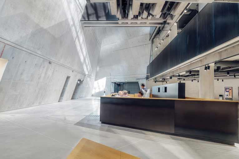 L'accueil du musée prend place sous la tour penché de verre, à 4,50 m sous l'esplanade. [©Studio d'architecture Kwadrat]
