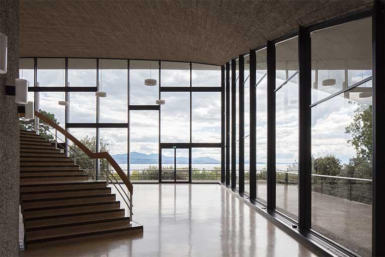 De 1961 à 1962, Jean Tschumi construit, en partenariat avec l'ingénieur François Panchaud, l'Aula-des-Cèdres à Lausanne. Cette collaboration entre les deux hommes est à l'origine d'immenses voiles de béton reflétant le bâtiment. [©Christian-Richters]
