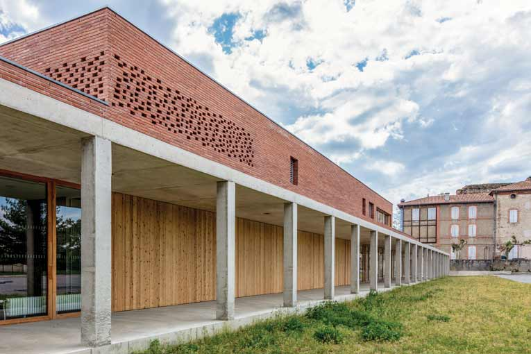 Vue de la façade intérieure du réfectoire, du préau et du parc de l'établissement. Au fond, le bâtiment existant. [©Cros & Leclercq Architectes]