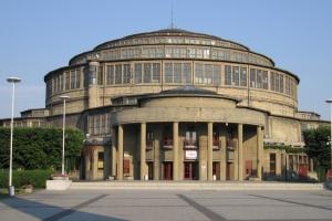 L'entrée principale de la Halle du Centenaire. Le dôme est couvert d'un toit en escalier flanqué d'une multitude de fenêtres, dont l'entourage est constitué d'un bois dur exotique. [©DR]