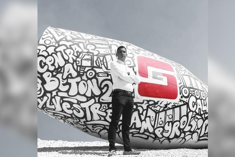 Rudy Sylvestre, gérant du groupe éponyme, devant l'iconique boule de toupie à l'entrée du site de Maubec, signée Namek. [©Groupe Sylvestre]