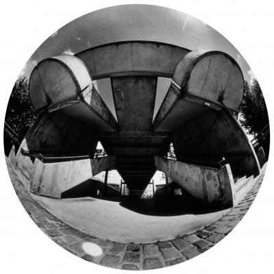 """Qui reconnaît une partie de la Cité des Sciences et de l'Industrie, à La Villette, Paris XIXe ? Cette photo argentique avec un fisheye, donne un grain, un rendu et une perspective """"extra-ordinaires"""". Par sa lenteur de prise, ce procédé photographique aléatoire enlève tout mouvement à l'espace urbain, entraînant une confusion entre le passé et le futur. Ici s'élève une """"Spider"""" (Araignée). ©Seka"""