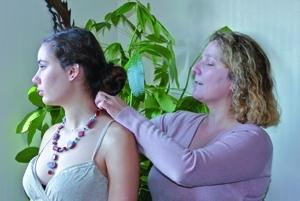 """Sandrine Mansoutre en train de placer un collier (""""Essaouira"""") autour du cou d'un modèle (Marie, sa nièce… l'égérie de Tutti Concreti). Ce collier est constitué de perles en béton teinté dans la masse avec des pigments rouge et bleu. Une histoire de femmes ! [©Photos Tutti Concreti]"""