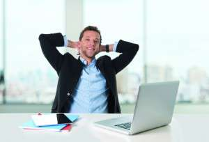 attractive businessman happy at work smiling relaxed at computer